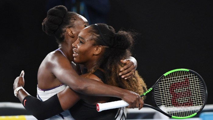 Serena Williams (R) hugs her sister Venus Williams