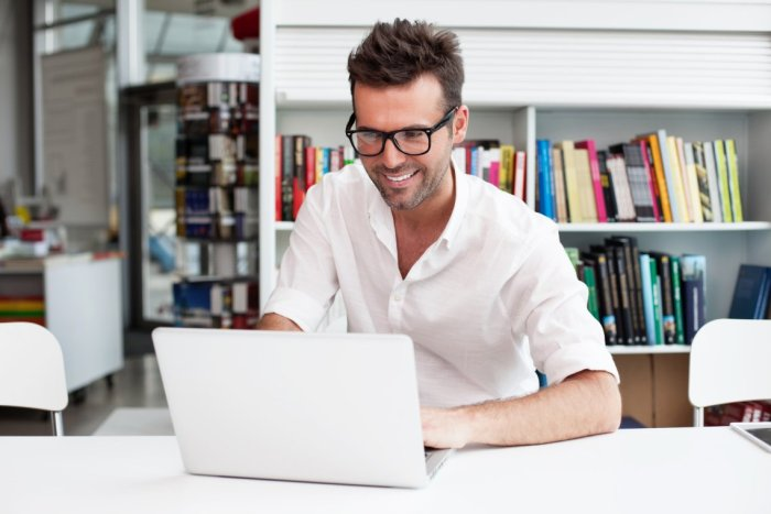 Happy man working on laptop in library
