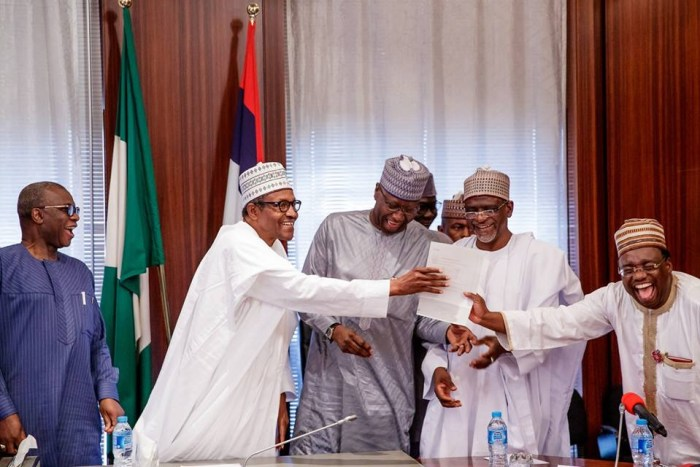 A WAEC official presents an attestation certificate to President Muhammadu Buhari in Aso Rock on November 2, 2018