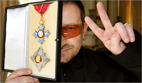 "Speaking of mixing entertainment with high power, here's Bono showing off an award he received from Queen Elizabeth II – the same queen that gave an award to mass abuser Jimmy Savile. Let's call this the occult elite award. Note the underlying ""one eye"" theme in the photo. Click to enlarge"