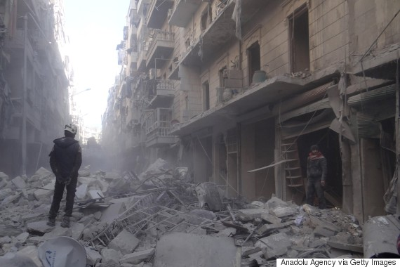 A civil defense team member stands on the debris of a building after a suspected Russian airstrike in Aleppo, Syria on Feb. 5, 2016