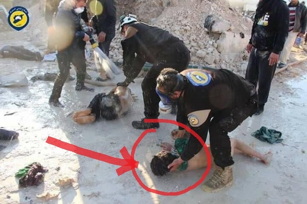 Image released by the Syrian White Helmets which shows rescue workers handling victims with their bare hands and inadequate gas masks, undermining claims of sarin usage. Click to enlarge