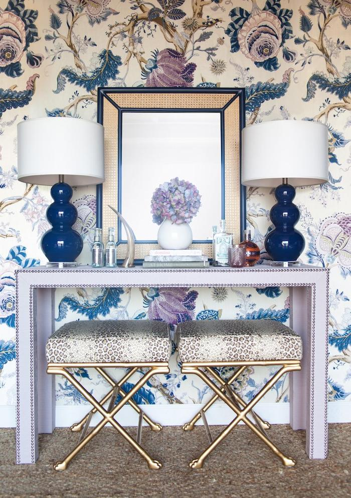30. Console Table at entrance styling it with beautiful lamp shades in symmetry, frames, upholstered stools with brass, in shades of pastels, fancy floral wallpaper in the theme color of ocean