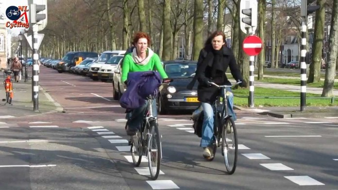Two woman bike without helmets on a street with a bike lane.