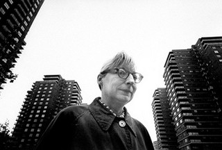 Jane Jacobs in glasses with apartment towers in the background.
