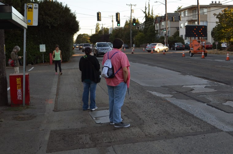 People wait for the bus on Greenwood Avenue N. and NW 117th St. To access this stop pedestrians run a gauntlet of parked cars, bushes in the public ROW and speeding cars. (photo by author)