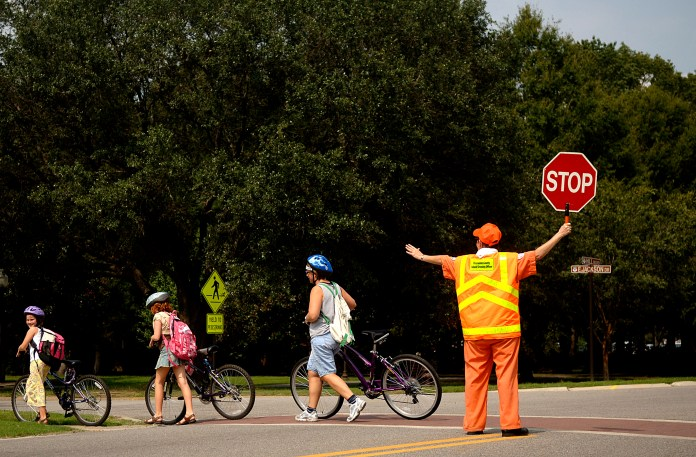 School crossing guards are a low paid, but essential position. Seattle Public Schools has struggled to recruit and train school crossing guards in recent years. (Credit: Nicholas Pilch)