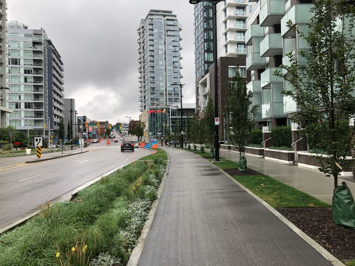 Quebec Street is a right-of-way wider than Aurora but features sidewalks with landscape buffers, protected bike lanes, and engaged street frontage. (Image by the author)