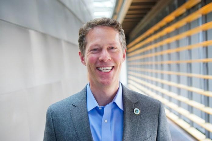 Alex Pedersen poses in a suitcoat in a City Hall hallway