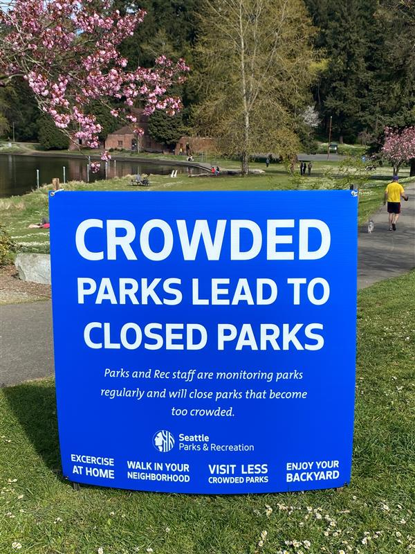 """""""Crowded parks lead to closed parks,"""" reads the City's sign at Seward Park, suggesting people stay home or in their yards instead."""