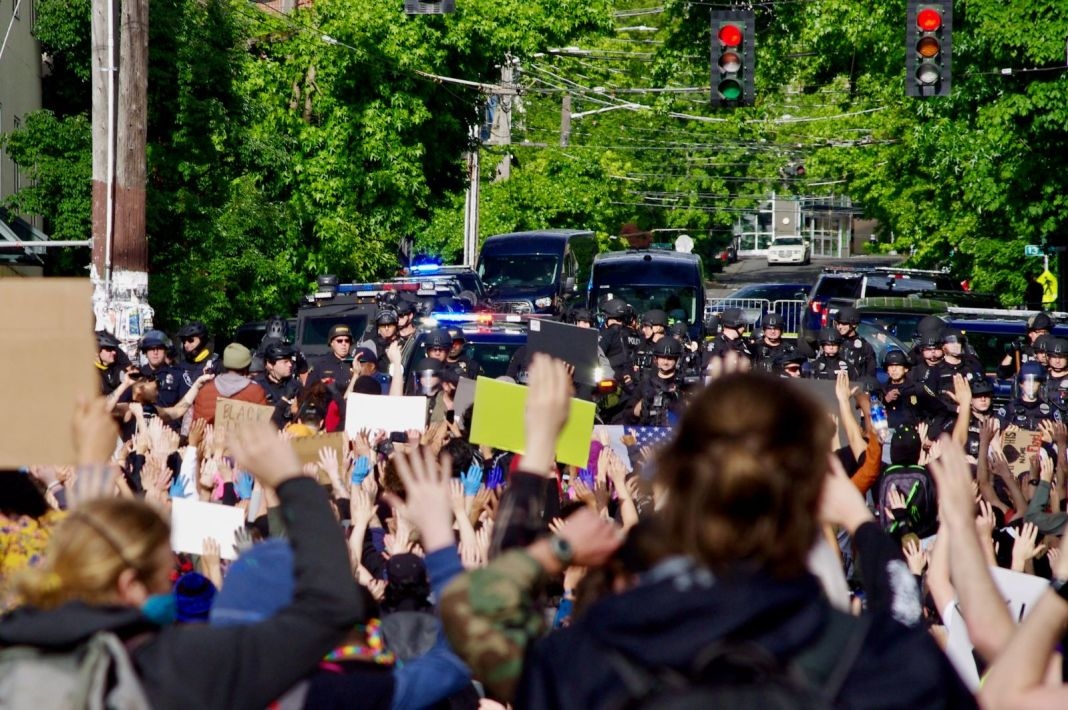 "Protestors gather behind a police barricade at the East Precinct building, chanting ""Hands up, don't shoot,"" on Sunday, May 31."