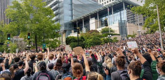 Protesters react with fists raised in solidarity as Nikkita Oliver takes the stage at City Hall on Wednesday June 3rd. (Photo by Doug Trumm)