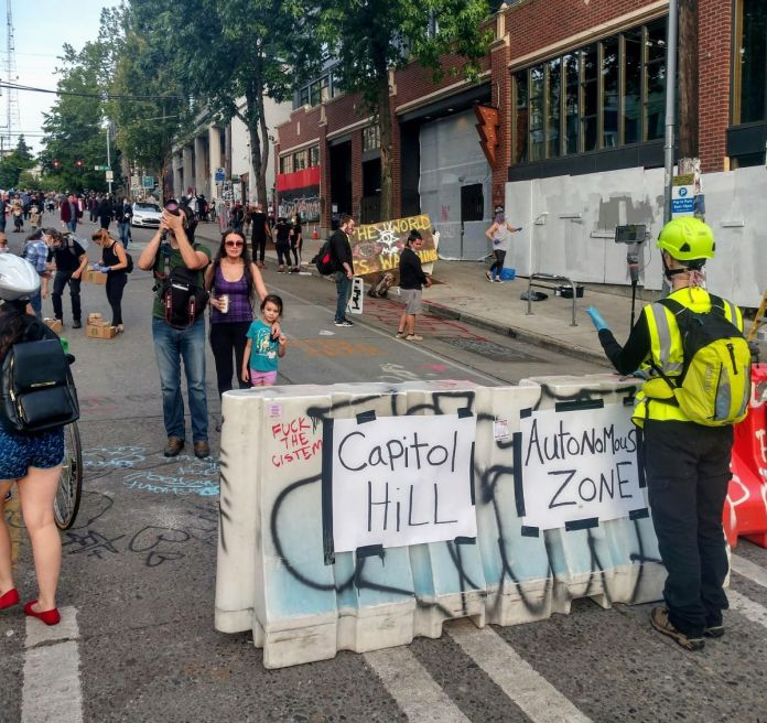 "People snap pictures and wander around surrounded by street art. A construction barrier that announces ""Capitol Hill Autonomous Zone"" (Photo by Doug Trumm)"