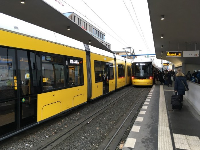 Yellow modern trams in a Berlin transit station.