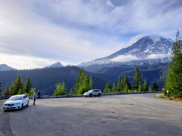 Clouds crown Mount Rainier as a few cars stop for passengers to take in the view.
