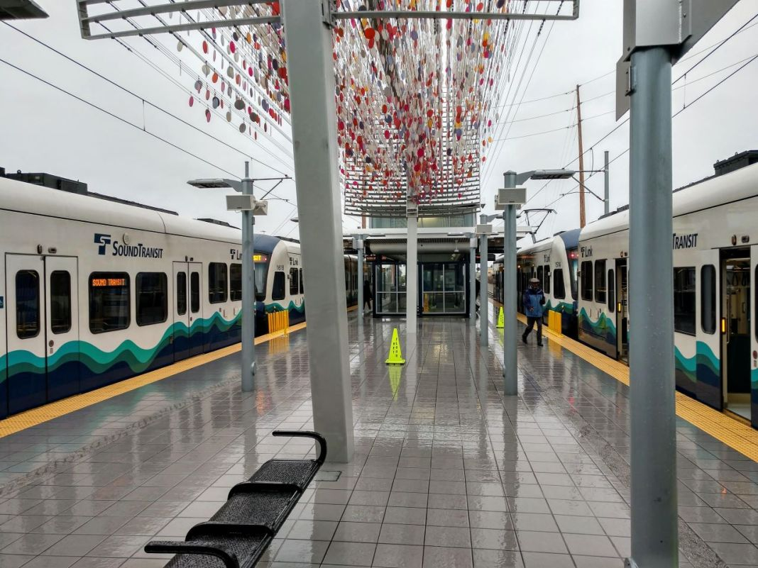 two trains at a station with little glass orbs sculpture overhead