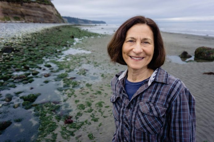 Angie Homola stands next to Puget Sound, a ubiquitous presence in the 10th, for this campaign photo.