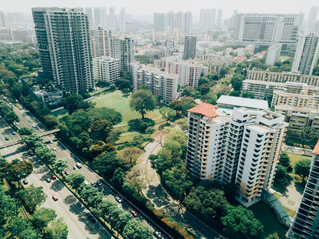 Residential towers and tree-lined streets with haze on the horizon.