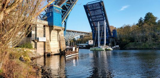 The Fremont Bridge goes up to let a catamaran pass.