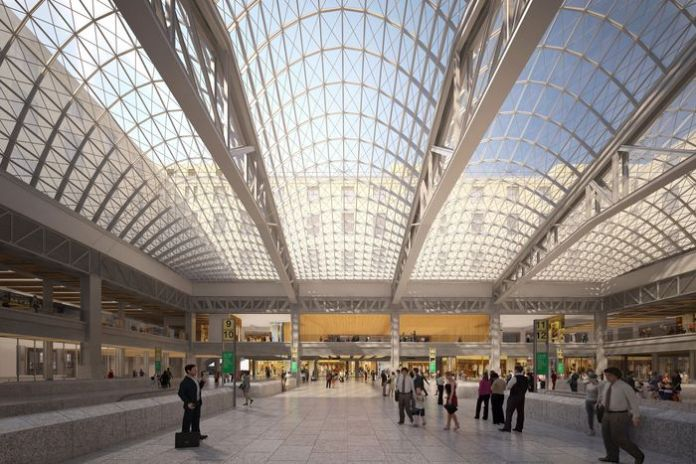 An airy train station with a glass ceiling held by steel latticework.