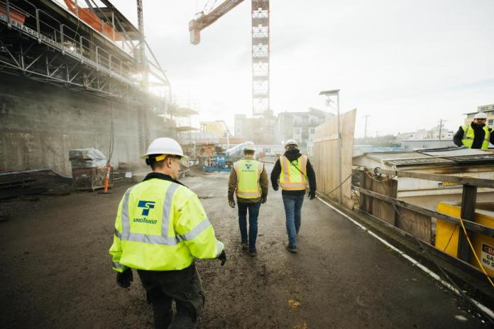 Three construction workers in Sound Transit vests walk a construction site with crane overhead.