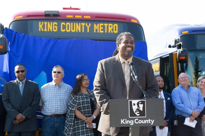 Terry White at a podium in front of a Metro bus flanked by Metro coworkers at a 2018 event.