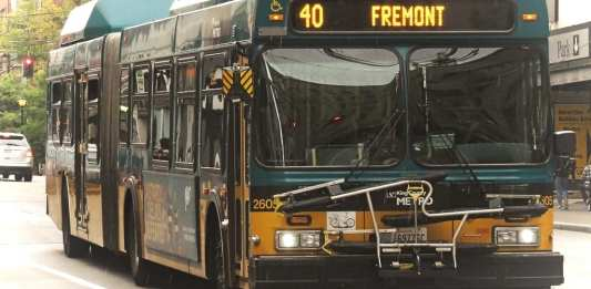 A green and yellow Route 40 with Fremont displayed on its screen with downtown towers in background.