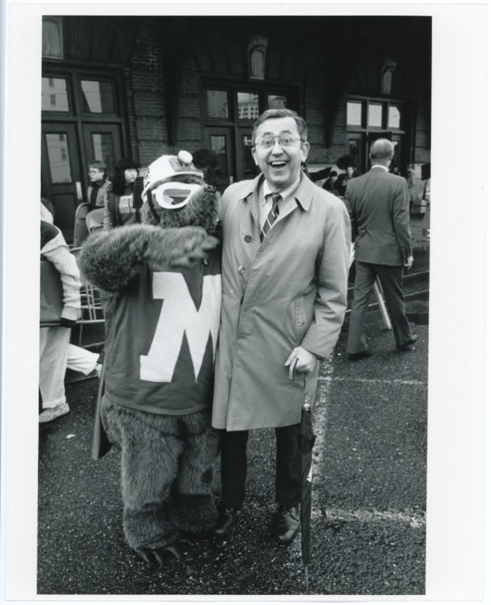 A mole mascot with goggles, a construction hat, and a big M on its chest poses with a dapper-looking man on the street.