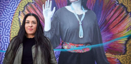 Colleen Echohawk with a colorful mural in the background showing an indigenous with a handprint over her lips.
