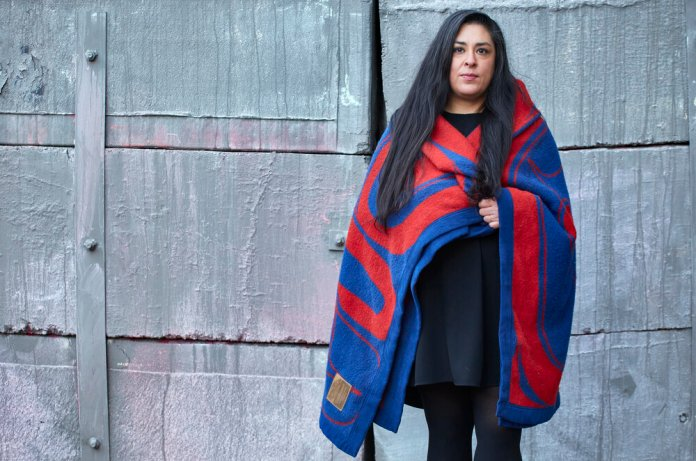 Colleen Echohawk where a blue blanket with red design.