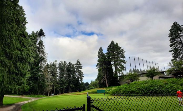 A golf course and driving range with a fence in the foreground.