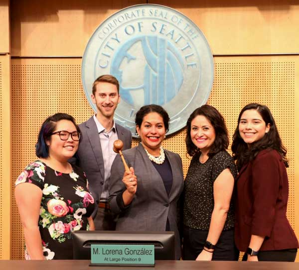 Brianna Thomas holds the gavel and poses next to Councilmember Gonzalez and her fellow staff members in Council Chambers.