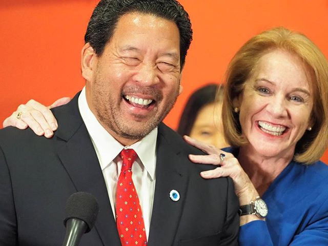 Mayor Durkan gives Bruce Harrell a squeeze on the shoulders.