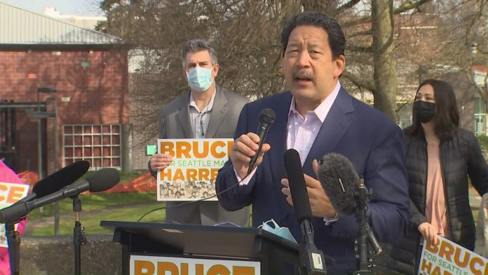 Bruce Harrell in a suitcoast with a microphone in hand at his candidacy announcement press conference.