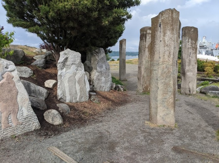 Carvings installed off the path symbolize the Chinese being expelled, pylons represent the Tacoma councilmembers. (Photo by author)