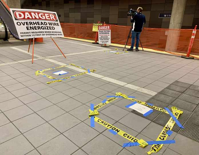 A photo shows a danger overhead wire  energized signs and caution tape installed on the station platform.