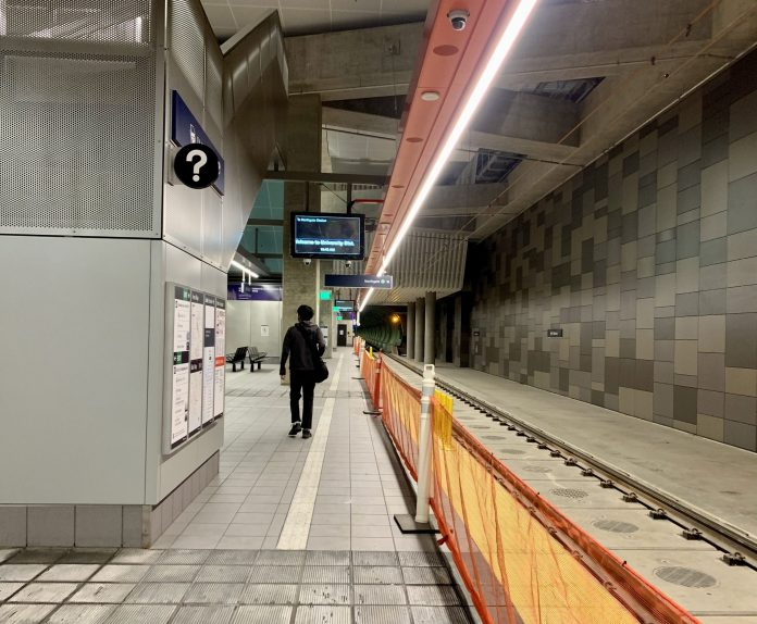 A photo of an underground light rail station platform. A man walks away from the camera. The train tracks are empty.