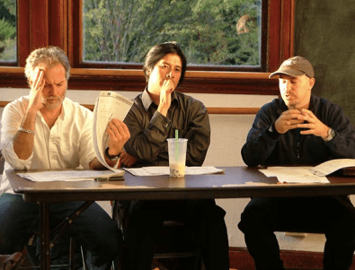 Photo of three men sitting at a table.