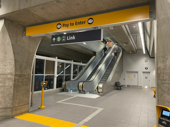 A photo showing the entrance to a light rail station with a yellow sign stating pay to enter and escalators appearing behind it.