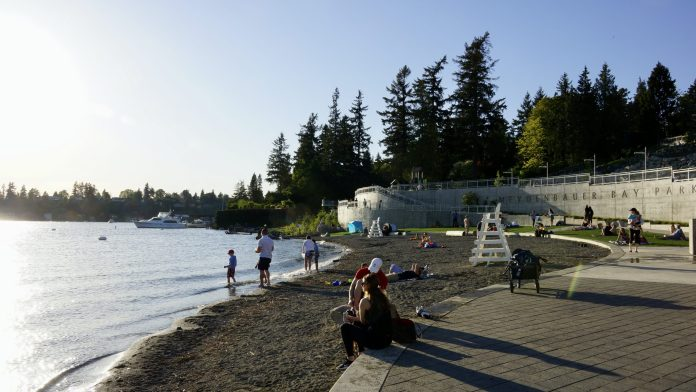 A photo of people sitting a small beach on a sunny day with evergreen trees in the background.
