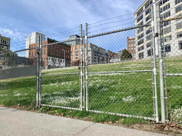 A photo of a chainlink fence surrounding a green field with tall buildings in the background.
