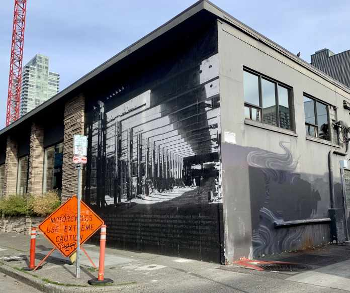 A photo of a black and white mural of a tunnel on the side of a one story building with a road construction sign in front of it.