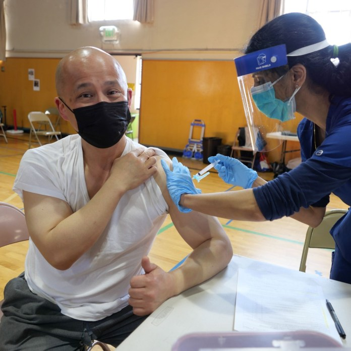 A health worker vaccinates a man wearing a face mask in a gymnasium.