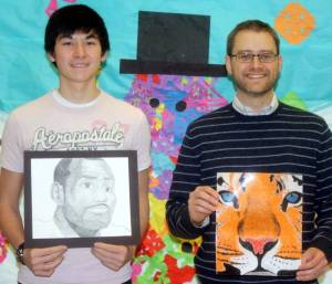 Jacob Leung presents his drawings of a tiger and Lebron James to Chris Kannel.