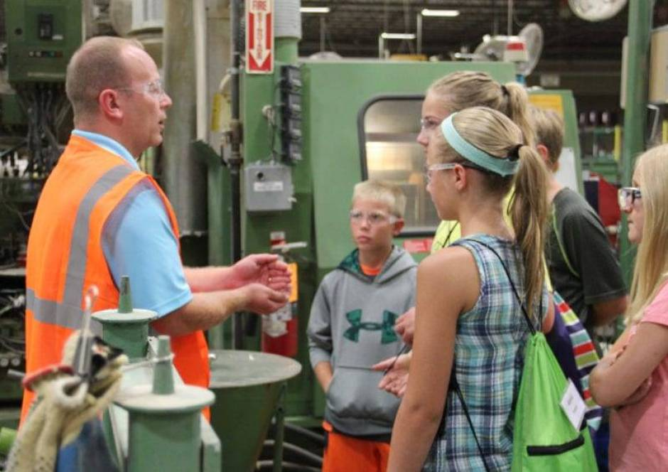 Students look on as David Meyer, Director of Quality Assurance and Continuous Improvement at Sauder Woodworking explains the processes needed to create a finished piece of furniture.
