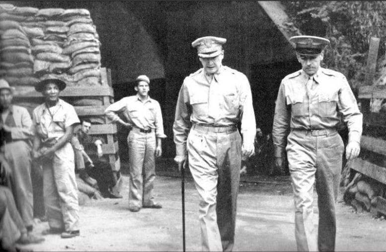 Four starred General MacArthur and two starred Chief of Staff, General Sutherland, step briskly out of the main enterance to the Corregidor Tunnels. To the left with his hand upon his hip is Junior Wyse.