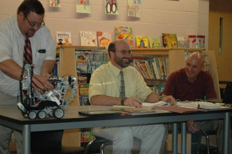 HS/MS Principal Roger Cade demonstrates a robotic elephant created by students at the recent school board meeting.