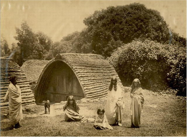 Toda people in front of their hut in the Nilgiri Hills.