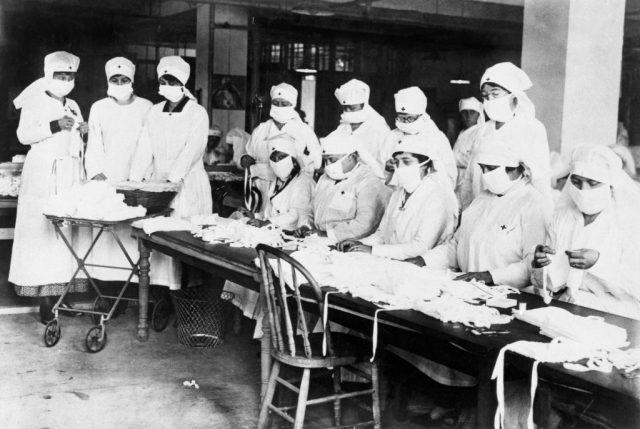ریڈ کراس والی خواتین کا ایک گروپ میز پر ماسک بنا رہا ہے۔