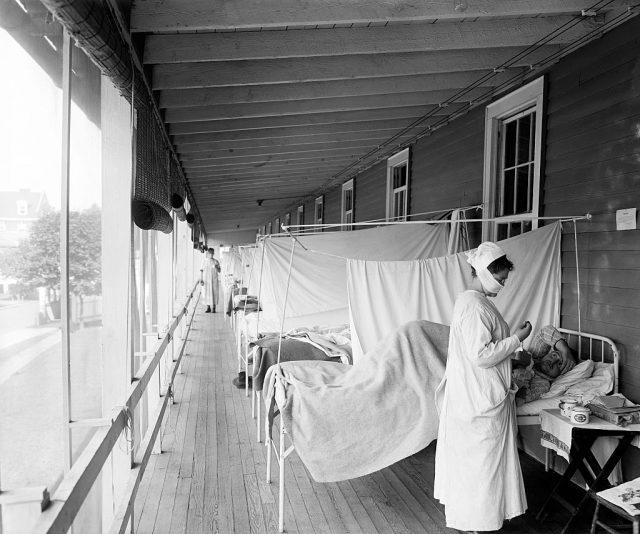 والٹر ریڈ ہسپتال کے فلو وارڈ میں ایک مریض کے ساتھ کھڑی ایک نرس۔